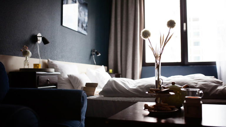 Dark model bedroom with vases and a large window