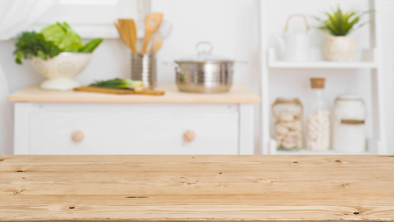 Wooden kitchen counter with decorative storage in the background